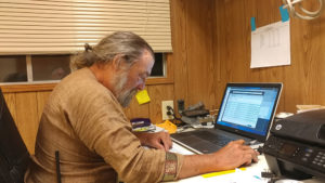 Viscount Edward working on a laptop in an office at Pennsic